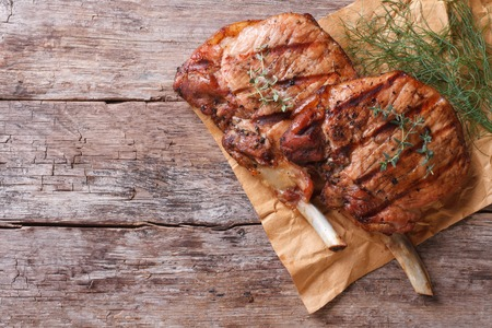 two pieces of of grilled pork with herbs on a paper on an old table top view horizontal close-up