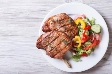 Schweinefleisch mit Salat aus frischem Gemüse auf einem weißen Teller gegrillt. eine Draufsicht auf einen horizontalen