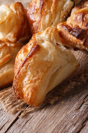 flaky: Pies of puff pastry close up on an old table. vertical