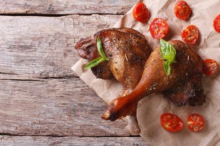 pato: dos patas de pato asado con albahaca y tomates de cerca en una mesa vieja Vista superior horizontal