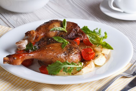 Tasty lunch: fried duck legs, with apples, tomatoes and herbs on a white plate closeup. horizontal   photo