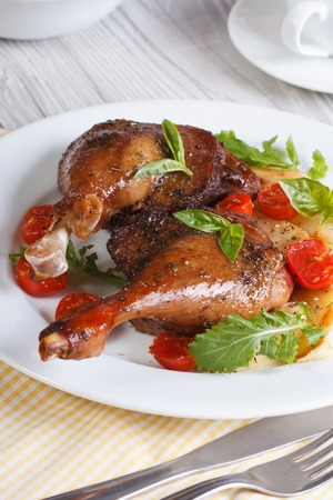 Delicious duck legs with apples on a white plate closeup vertical  photo