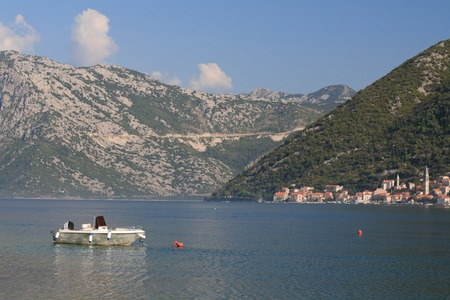 Morning in the Bay of Kotor in Montenegro. White boat on a background of mountains and the city of Perast photo