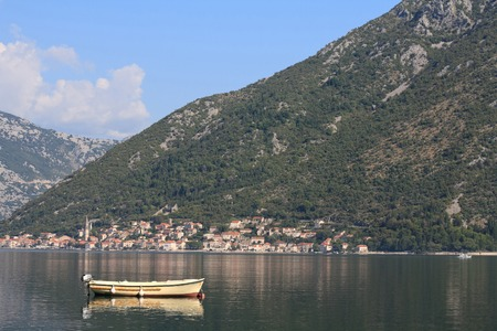 Bay of Kotor in Montenegro. Fishing boat in the morning on a background of mountains and the town of Perast photo