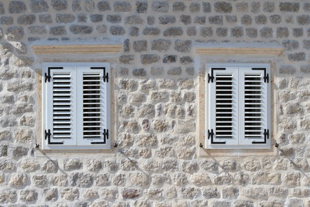 Two shuttered windows in the stone wall of the house, horizontal photo