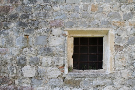 Small old square window with bars in a stone wall photo