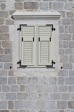 Window closed white shutters in Perast, Montenegro. close-up photo