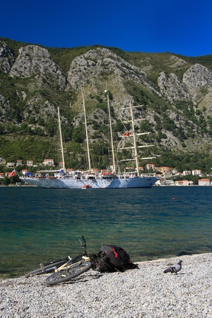 Large sailing ship Star Clippers in the Bay of Kotor and the bike with a backpack on the shore. Montenegro, September 28, 2014
