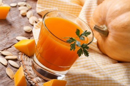 Pumpkin juice with pulp close-up on a table on a background of ripe vegetable photo