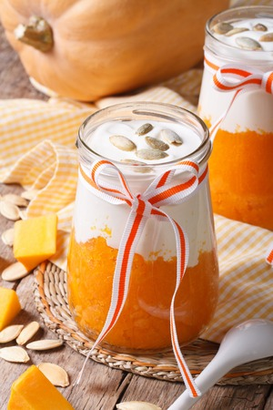 yellow ribbon: Delicious pumpkin with yogurt close up in jars