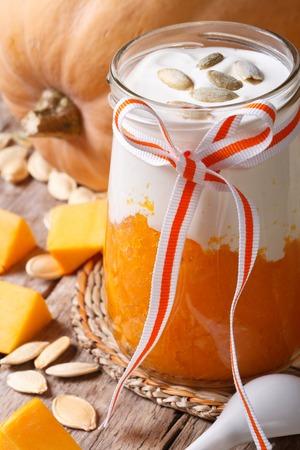 pumpkin dessert, yogurt and seeds in a jar closeup. vertical Stock Photo
