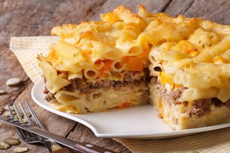 baked: Delicious appetizers: baked penne pasta with meat, cheese and pumpkin close up. horizontal Stock Photo