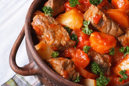 stew in tomato sauce with vegetables in a pot macro. horizontal top view