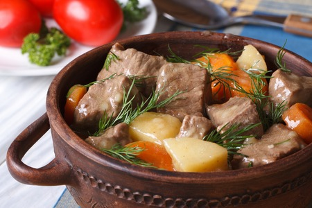 beef stew with vegetables in a pot close up. horizontal.