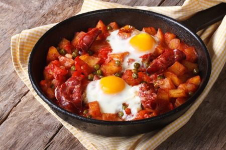 Spanish Food: eggs over Flemish, a pan closeup. horizontal