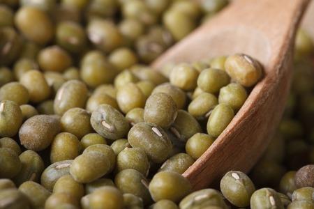 Raw green mung bean in wooden spoon macro. horizontal photo
