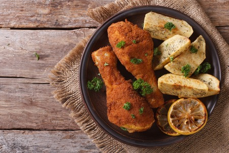 are fried: fried chicken legs dipped in batter, with potato on the plate closeup. top view of a rustic style. horizontal