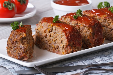 Sliced meat loaf with ketchup and parsley close-up on a plate, horizontal photo