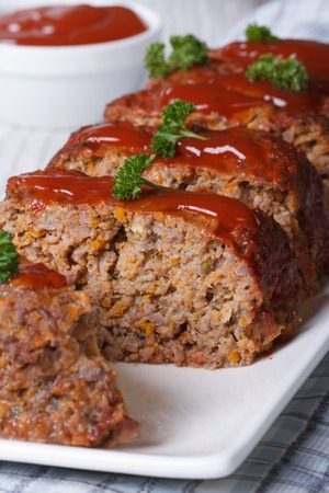 sliced meat loaf with ketchup and parsley close-up on a white plate, vertical photo