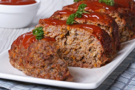 sliced meatloaf with ketchup and parsley closeup on a white plate, horizontal