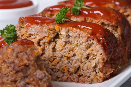 sliced meat loaf with tomato sauce on a white plate macro, horizontal photo