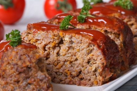 sliced meat loaf with ketchup macro on a background of ripe tomatoes, horizontal photo