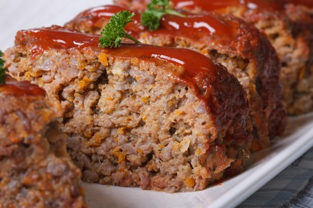 MEAT LOAF: Delicious meat loaf with ketchup on a white plate, macro horizontal Stock Photo