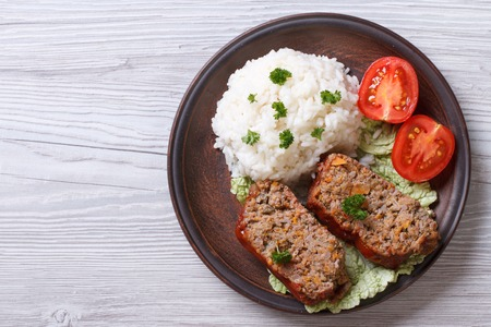 Delicious meat loaf with rice on a plate on the table, a horizontal top view photo