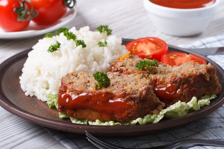 sliced meat loaf with rice and vegetables on a plate close-up, horizontal photo