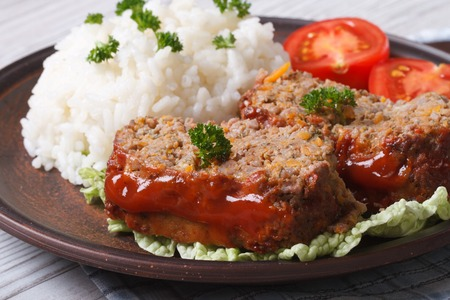 Delicious meatloaf with rice and tomatoes on a plate close-up, horizontal photo