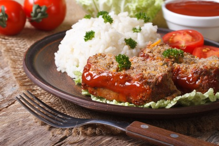 pieces of meat loaf and rice on a plate close-up, horizontal photo