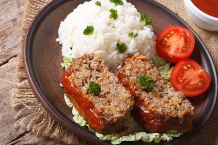 Delicious meat loaf with rice on a plate on a table in a rustic style, horizontal photo
