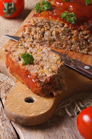 meat loaf with vegetables close-up on a cutting board. vertical photo
