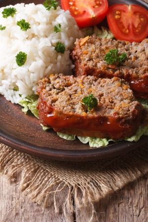 meat loaf with rice and vegetables on a plate close-up, vertical photo