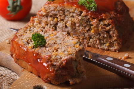 meat loaf with ketchup and vegetables close-up on chopping board. horizontal photo