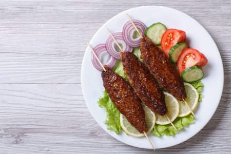Kebab of minced meat on wooden skewers on a plate with vegetables. top view, horizontal, close-up photo