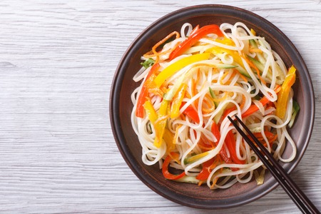 Rice noodles with vegetables close-up on a plate with chopsticks. horizontal view from above Banque d'images