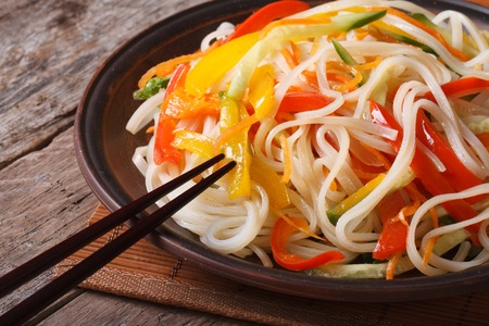 Rice noodles with peppers, carrots and zucchini close-up on a plate. a horizontal Stock Photo