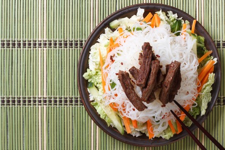 Delicious Asian salad rice noodles and meat with chopsticks. horizontal view from above photo