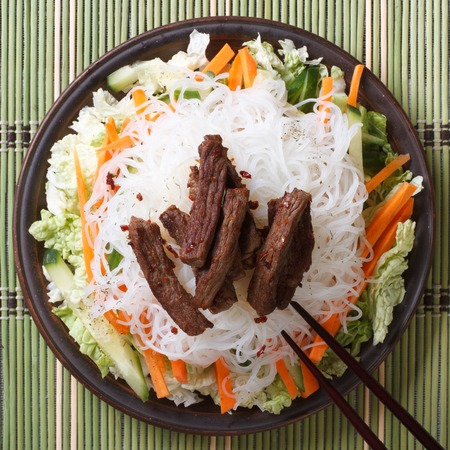 Asian rice noodles with meat and vegetables close-up and chopsticks. view from above photo