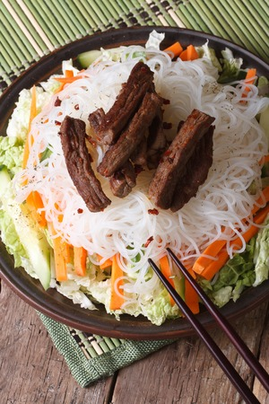 Asian rice noodles with meat and vegetables close-up and chopsticks on the table. vertical photo