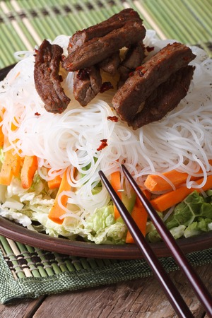 Salad of rice noodles with meat and vegetables close-up and chopsticks on the table. vertical photo