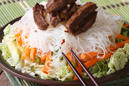 rice noodles with slices of meat and vegetables close-up on the table. horizontal photo