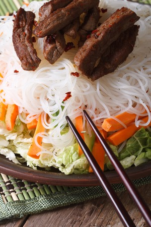 rice noodles with slices of meat and vegetables close-up on a plate. vertical photo