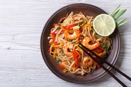 thailand view: Rice noodles with shrimps and vegetables close-up on the table Stock Photo