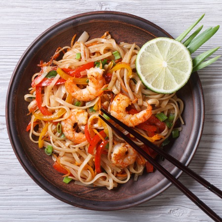 Delicious rice noodles with shrimp and vegetables close-up on a plate