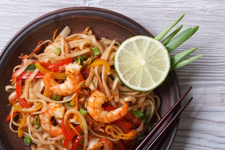 Asian rice noodles with shrimp and vegetables close-up on the table
