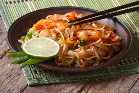 Asian food: rice noodles with shrimp and vegetables close-up on a plate