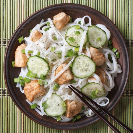 rice noodles with chicken and vegetables close up on a plate photo