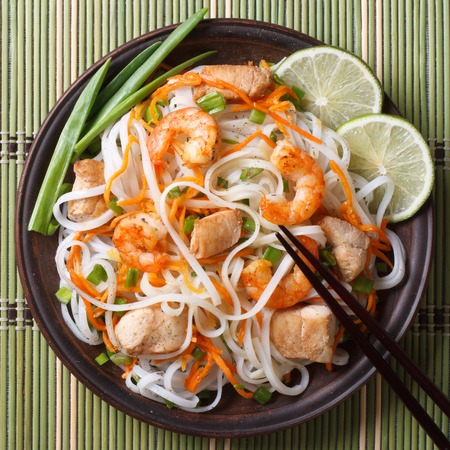 rice noodles with chicken, shrimp and vegetables closeup photo